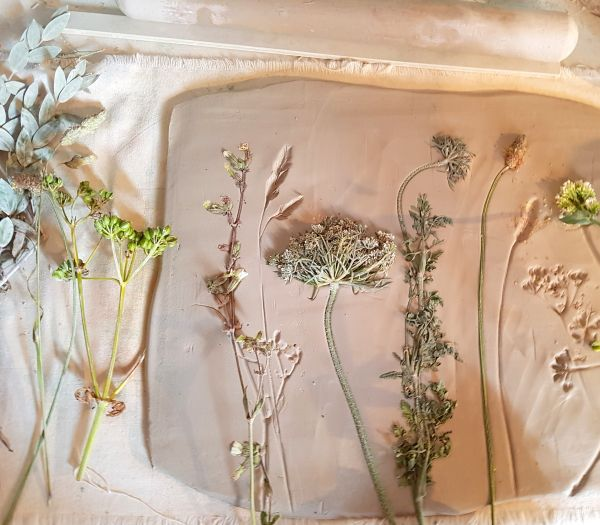 impressing wild flowers into clay
