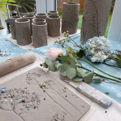 pressing flowers into clay